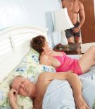 Big-titted red-haired grandma Bea Cummins jacking off huge dick while cuck husband sleeps