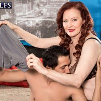 Redhead GILF crosses her bare legs prior to sexual relations with a younger man