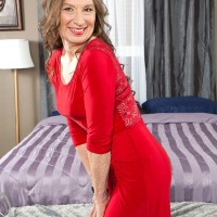 Mature woman awaits her much younger lover on a bed in a red dress and nylons