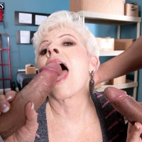 Clothed granny gets on her knees to give 2 large cocks oral sex in warehouse