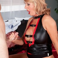 Gorgeous blonde granny gives a younger man a blowjob in a pleather dress