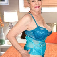 Short haired granny has her great tits freed from a brassiere by her lover boy