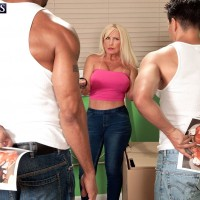 Hot MILF over 60 with blonde hair seduces younger men in a tube top and jeans