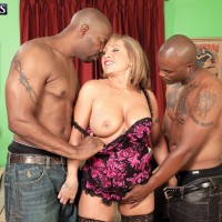 Sexy granny tugs on a couple of younger men's big black dicks at once in the nude