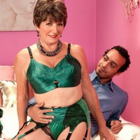 Sexy granny greets her younger Latino lover in satin lingerie paired with nylons