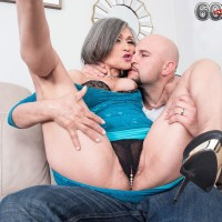 60 plus grandma Kokie Del Coco seduces a younger boy in a short sundress on the couch