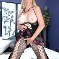 Ash-blonde granny Charlie whips out her huge titties in over the knee boots and mesh body-stocking