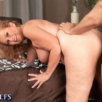 Big-boobed golden-haired grandma giving blow job on knees before hard-core doggy style sex