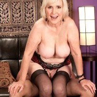 Busty aged XXX film star Lola Lee providing oral pleasure in pantyhose and lingerie