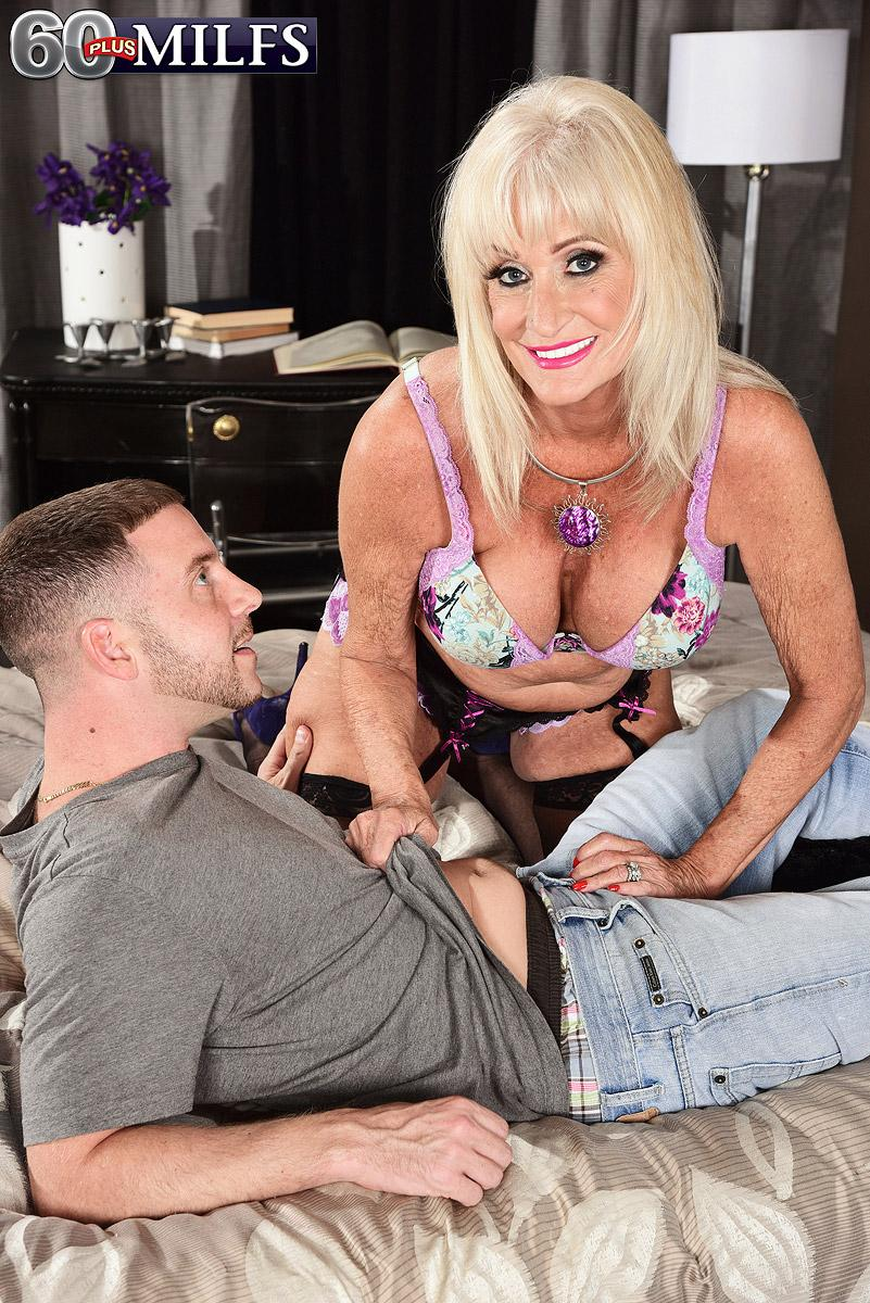 Fair-haired grannie Leah L'Amour gives her man toy a HJ in lingerie and hosiery