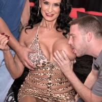 Mature dark haired pornographic starlet Rita Daniels showing off no panty upskirt during breast sucking