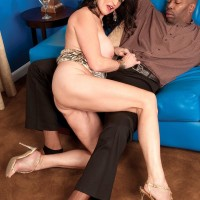 Older black-haired XXX adult starlet Rita Daniels revealing gigantic hooters before interracial sex