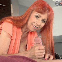 Redheaded grannie with excellent gams and immense natural tits delivering hand-job in kitchen