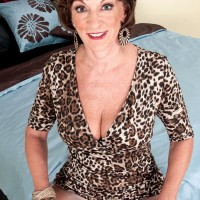 Solo grandmother Sydni Lane teasing on bed by showcasing melon-holder in hosiery