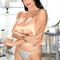 Top aged X-rated film star Rita Daniels uncovers her big boobies and flashes her bloomers too